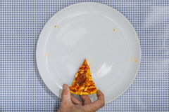 Eating a Pizza Salami, high angle view. Eating a Pizza Salami on white plate, on blue checkered table cloth, part of an image series, high angle view from above Stock Image