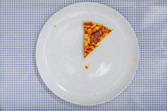 Eating a Pizza Salami, high angle view. Eating a Pizza Salami on white plate, on blue checkered table cloth, part of an image series, high angle view from above Royalty Free Stock Images
