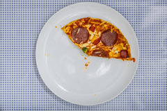 Eating a Pizza Salami, high angle view. Eating a Pizza Salami on white plate, on blue checkered table cloth, part of an image series, high angle view from above Royalty Free Stock Photos