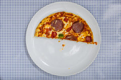 Eating a Pizza Salami, high angle view. Eating a Pizza Salami on white plate, on blue checkered table cloth, part of an image series, high angle view from above Stock Photography