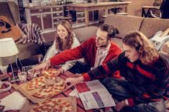 Participants of music band eating pizza after composing music. Eating pizza. Three creative participants of music band eating pizza after composing music stock image