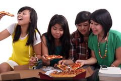 Eating pizza together. Teenage girls sitting and eating pizza Royalty Free Stock Image