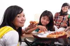 Eating pizza together. Group of young  woman sitting and eating pizza Stock Images