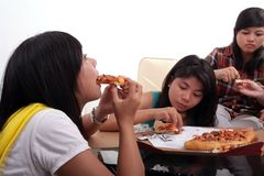 Eating pizza together. Group of young  woman sitting and eating pizza Stock Photos