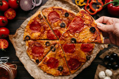 Eating pizza, top view. Hand taking slice of hot delicious pizza, selective focus. Pizza ingredients on the wooden table royalty free stock photography