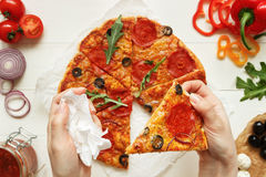 Eating pizza, top view. Hand taking slice of hot delisious pizza. Pizza ingredients on the wooden table royalty free stock image