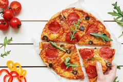 Eating pizza, top view. Hand taking slice of hot delisious pizza on the white wooden table stock images