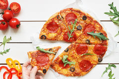 Eating pizza, top view. Hand taking slice of hot delisious pizza on the white wooden table Royalty Free Stock Photos