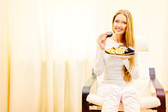 Eating with pleasure. Happy slim girl with pleasure eats tasty cookies with chocolate. Healthy eating. Diet Stock Images