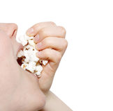 Eating popcorn. A girl eating a handful of  popcorn Royalty Free Stock Images