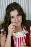 Eating popcorn. Young girl with a red shirt eating popcorn in a red bowl Stock Photos