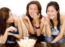 Eating Popcorn. Three attractive asian women have fun eating popcorn Stock Photo