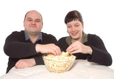 Eating popcorn. Man and woman eating popcorn Stock Images