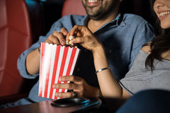 Eating popcorn at the movie theater. Man touching the hand of his date while grabbing some popcorn at the movie theater stock images