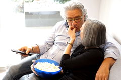 Eating popcorn and watching tv Royalty Free Stock Images