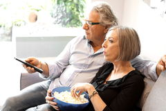 Eating popcorn and watching tv Stock Photos