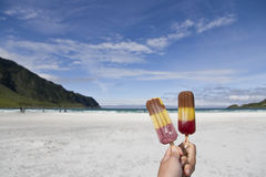 Eating popsicles at the beach. Eating popsicles at a white beach with surrounding mountains Stock Photography