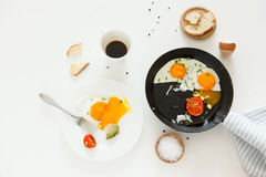 Eating in the process, fried eggs in a frying pan and on a plate, toast with avocado and a cup of coffee for breakfast. Royalty Free Stock Photo