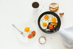 Eating in the process, fried eggs in a frying pan and on a plate, toast with avocado and a cup of coffee for breakfast. Royalty Free Stock Photography