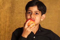 Eating a red apple. Asian healthy boy eating a red apple stock photography