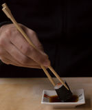 Eating a roll with chopsticks Royalty Free Stock Photo