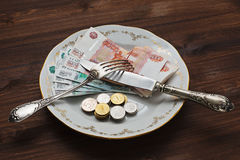 Eating russian rubles from the plate. Eating russian money, rubles, in bank notes and coins from the vintage plate with silverware stock photo