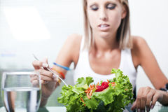 Eating a salad. Young women at home eating a salad Stock Photography