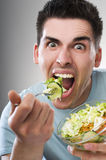 Eating salad. Young men eating salad close up shoot Stock Images