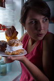 Eating in secret. Young beautiful woman eating cakes in secret Stock Photography