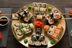 Eating set of sushi maki and rolls in japanese resaturant. Japanese restaurant, eating sushi roll platter at rustic wood background. Set for two with chopsticks Royalty Free Stock Photo