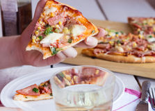 Eating a slice of pizza hands. Pizza with sausage, chicken, corn and cheese, Italian cuisine Stock Images