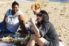 Eating snack. Intercultural young people having snack while relaxing on sandy beach on weekend Royalty Free Stock Photos