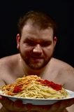 Eating spaghetti. This is a picture of a fat man eating pasta with tomato sauce Royalty Free Stock Photo