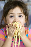 Eating Spaghetti. Little girl eating spaghetti with her hands Stock Photos