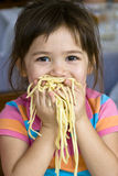 Eating Spaghetti. Little girl eating spaghetti with her hands Stock Images