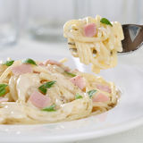 Eating Spaghetti Carbonara noodles pasta meal on a plate with fo Stock Photo