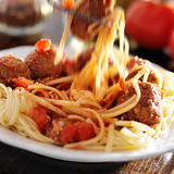 Eating spaghetti and meatballs with visible motion blur stock photo