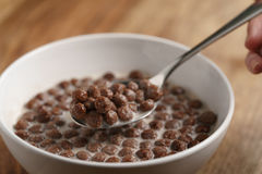 Eating with spoon chocolate cereal balls with milk in white bowl for breakfast on wooden table Stock Images
