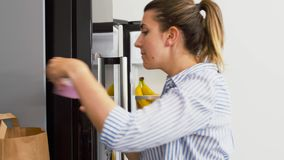 Woman putting new purchased food to home fridge stock footage