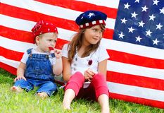 Eating suckers. Two children sitting next to an american flag eating suckers Royalty Free Stock Photo