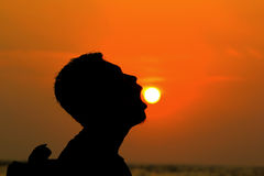 Eating the sun. Young man eating the sun Stock Image