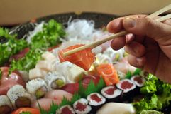 Eating sushi. This is a close up view of a hand grabbing a piece of salmon from a sushi plate Royalty Free Stock Photo