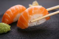 Eating sushi. Delicious Japanese cuisine, nigiri sushi with salm. On served with wasabi and ginger, close up. Restaurant concept royalty free stock photography