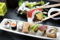Eating sushi roll using chopsticks Royalty Free Stock Images