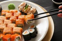 Eating sushi rolls at japanese food restaurant Stock Photos