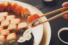 Eating sushi rolls at japanese food restaurant Stock Photo