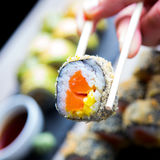 Eating Sushi. Eating a salmon sushi roll filled with some curry Royalty Free Stock Photos