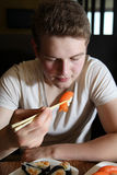 Eating Sushi. Young man holding peace of sushi with chopsticks, shallow focus Royalty Free Stock Photos