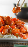 Eating sweet and sour chicken with chopsticks Stock Images