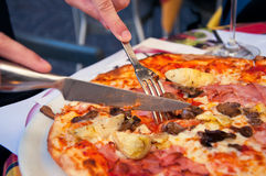 Eating tasty Italian pizza. Cutting a delicious Italian pizza with cheese, mushrooms, artichokes and tomatoes with help of knife and fork. Focus on fork Stock Images
